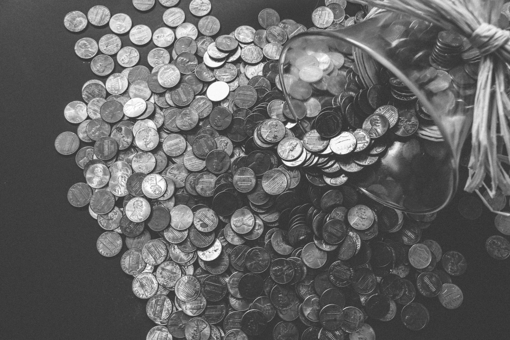 black and white photo of coins spilling out of a jar