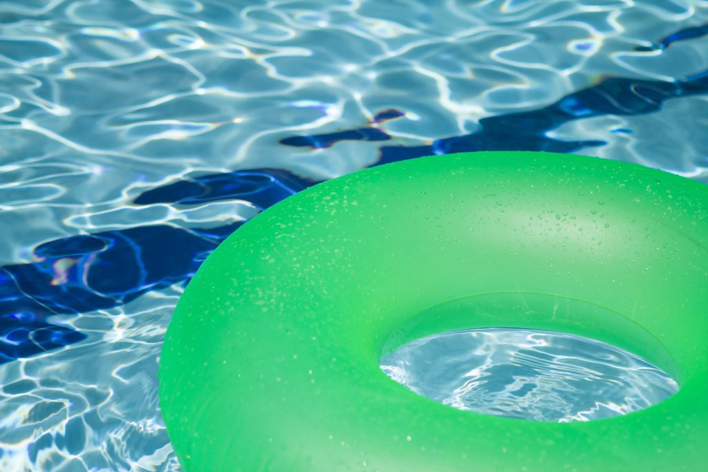 pool with a green inner tube on a sunny day
