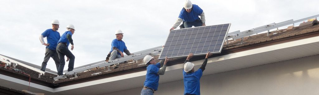 Men installing solar panels on roof