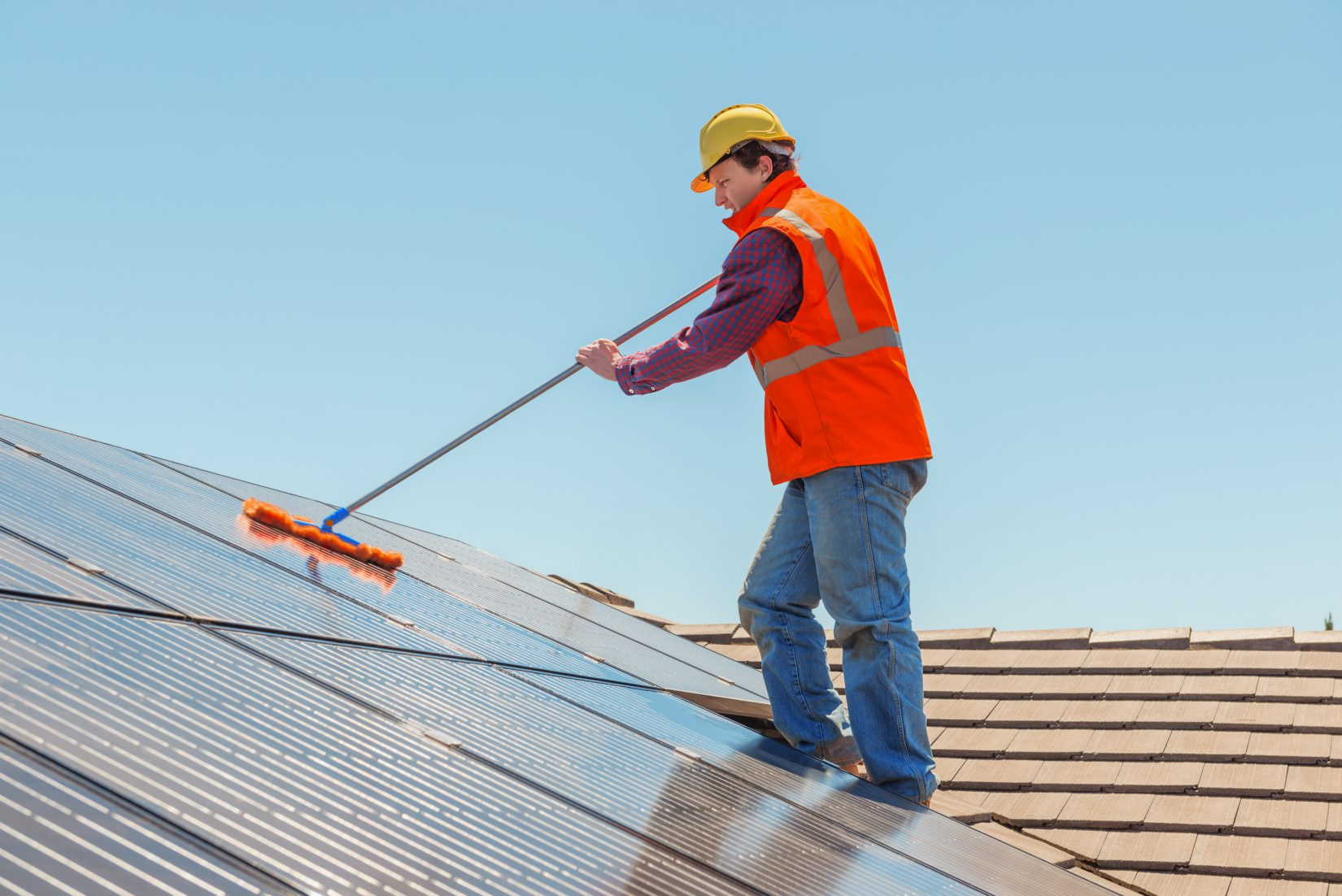 worker cleaning a solar panel on roof