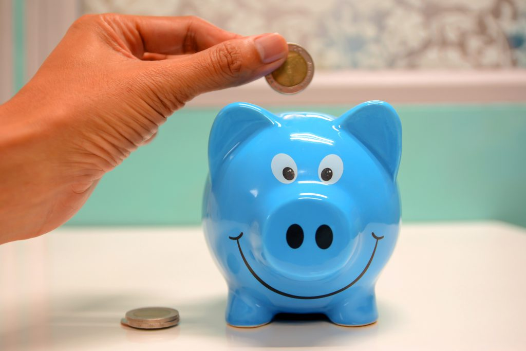 person dropping coins into a blue piggy bank