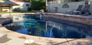 Landscaped backyard with a pool using solar pool heating systems