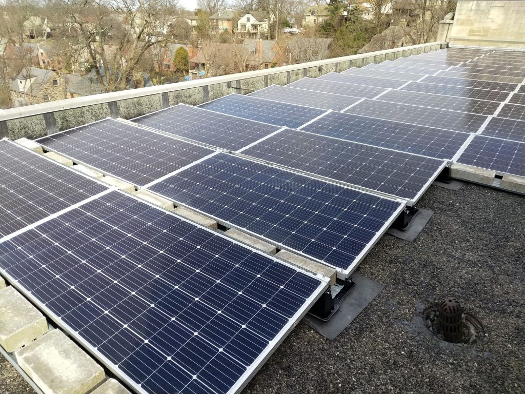 rows of solar panels installed on a building roof