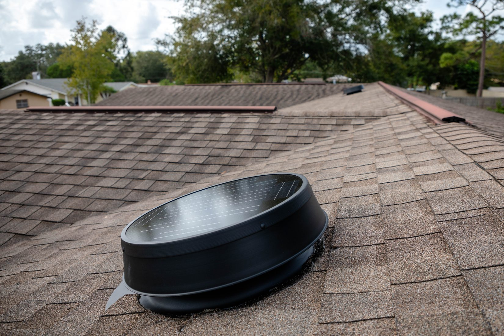 Side view of a solar attic fan unit on roof