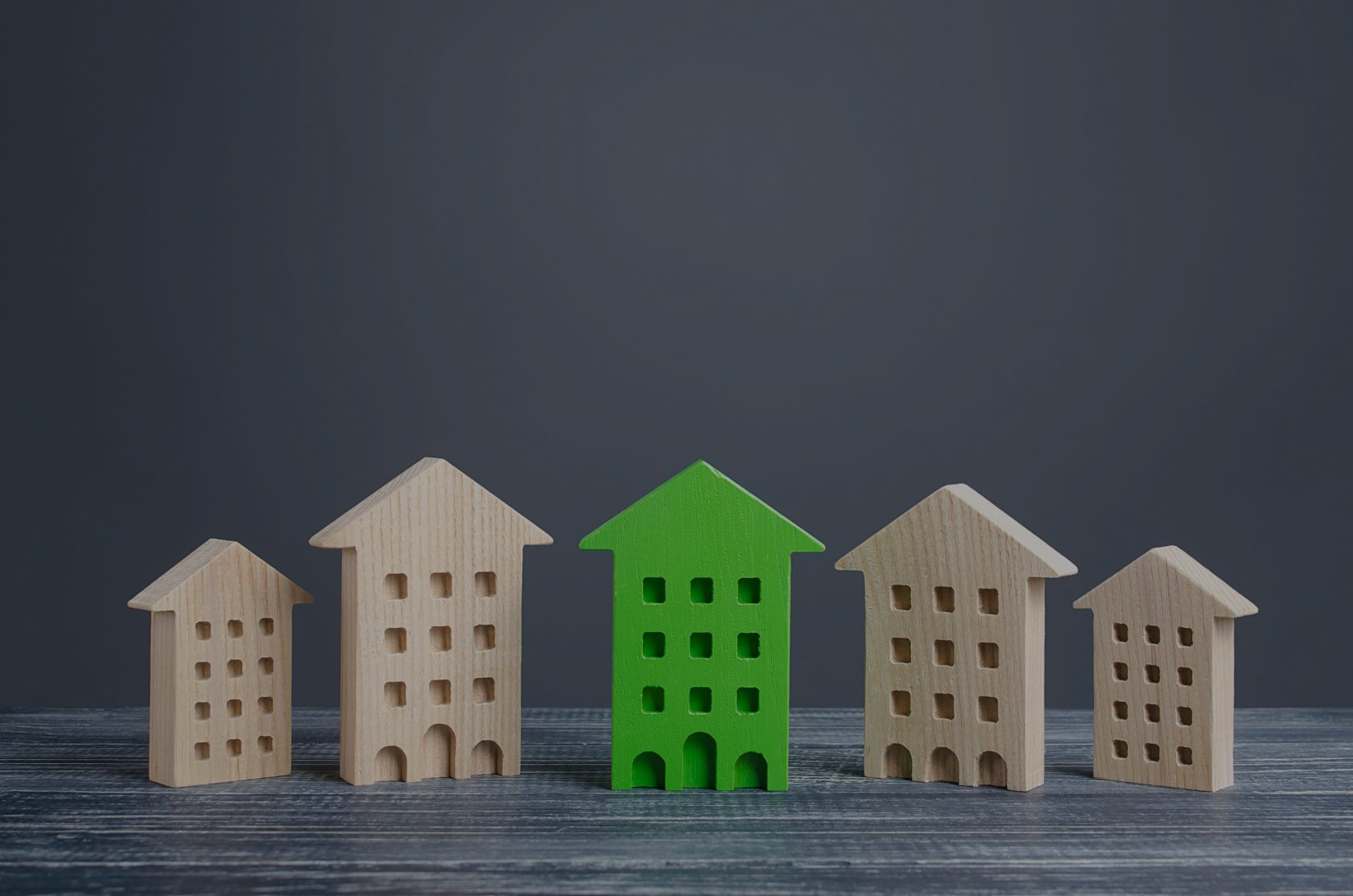 wooden toy houses with one green one in the center