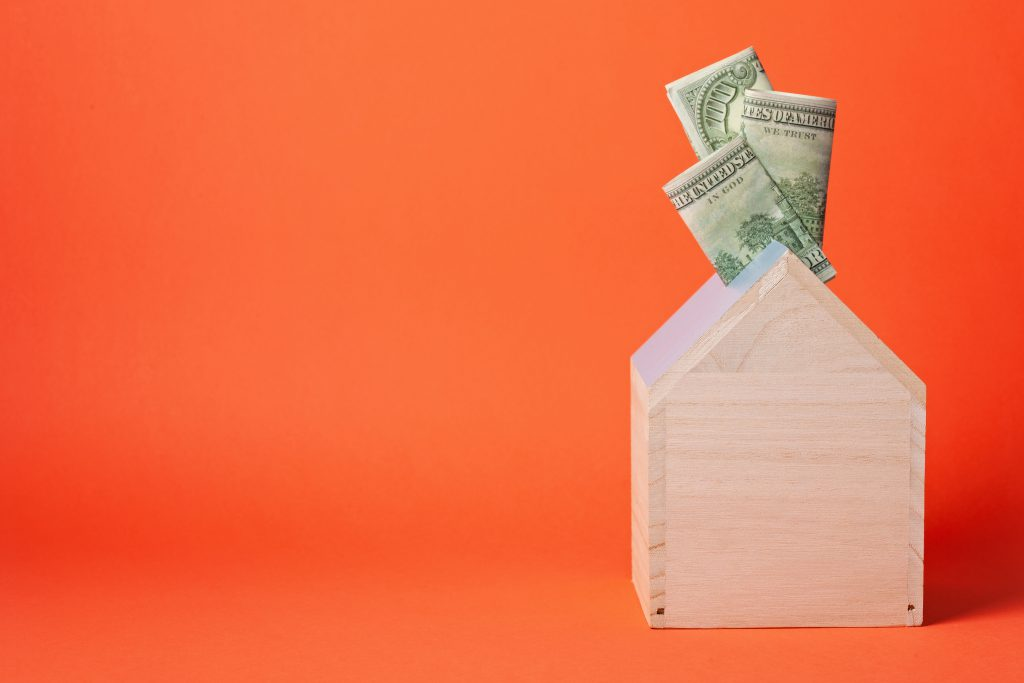 Wooden toy house with money sticking out of the top, set against an orange background